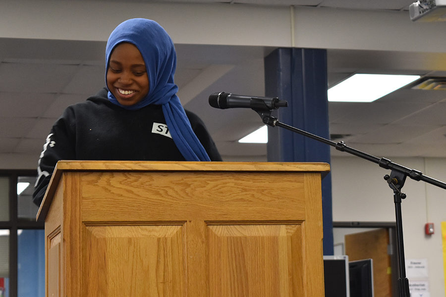 """Junior Maryam Oyebamiji laughs during her reading. Oyebamiji had been an audience member of the read-in for the last two years, but spontaneously chose to read this year. """"Mr. Welch kept egging me to go, he kept staring at me, and I was like, 'You know, why not,' and I already had a book in my hands so I went up,"""" Oyebamiji said."""