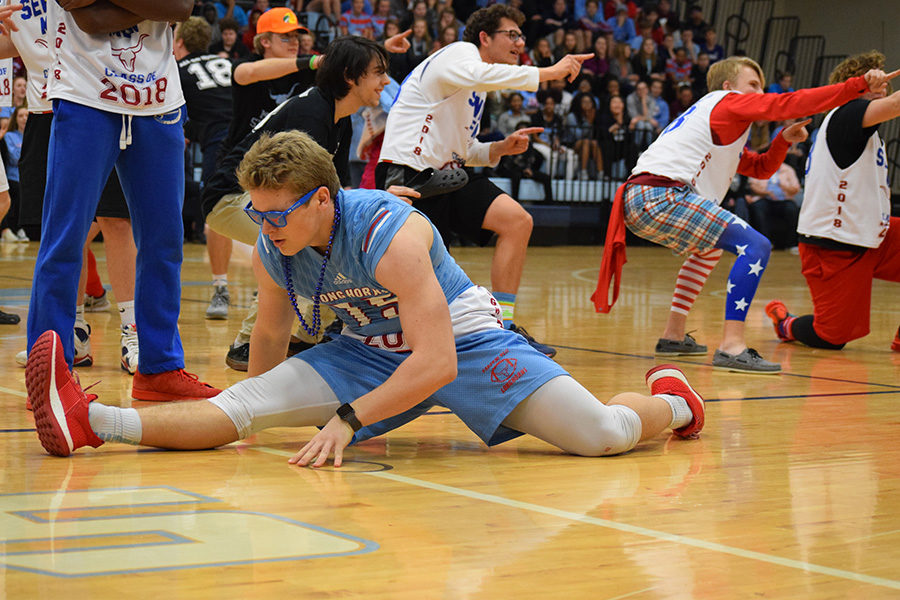 """Dropping into the splits, senior Clayton Jensen completes the final pose of their Mr. Longhorn dance. The pep rally was the first time Jensen showcased his splits during the dance. """"[The pep rally] was definitely more special. It was a feeling that I won't be able to experience ever again,"""" Jensen said."""