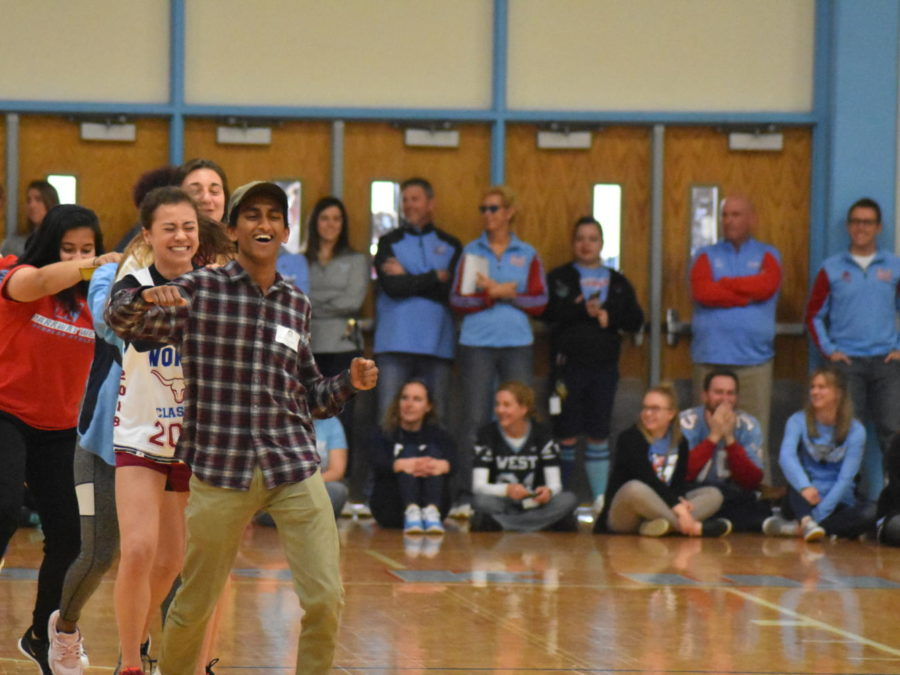 """Representing the girls' track and field team, senior Emily Dickson leads a conga line with Lafayette junior Bharat Sreekrishnavilas. """"Apparently Bharat didn't know what a conga line was, so he walked in like an elf. I knew [running in] was going to be crazy since there's about 100 people on the team,"""" Dickson said."""