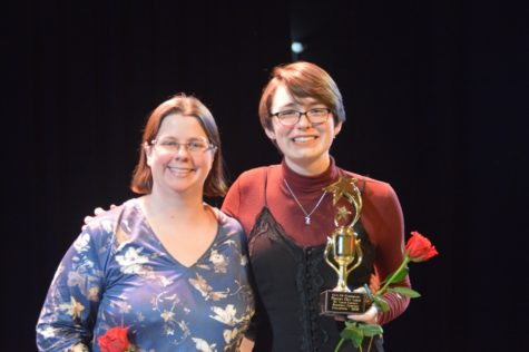 """Senior Ann Truka and English teacher Andria Benmuvhar pose with roses and the Regional Poetry Out Loud Champion trophy. Truka has competed in Poetry Out Loud for four years in a row. """"I was thrilled that Ann first won the school competition because she had won previously as a freshman. It felt like a nice bookend experience. The regional competition was very tight—everyone gave incredibly strong performances—so when Ann won I was very excited and proud of her,"""" Benmuvhar said."""