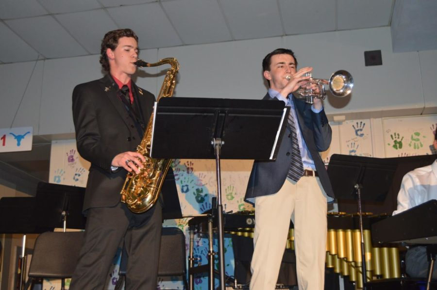 "Senior Jonah Hathaway and junior Noah Wright perform at the Jazz Coffee House concert. Both students are members of the jazz band led by band director Brad Wallace and choir director Brian Parrish. ""Jazz was a genre of music that I wasn't familiar with,"" Wright said. ""Being in Jazz Band has made me a better musician and has helped me to enjoy music even more."""
