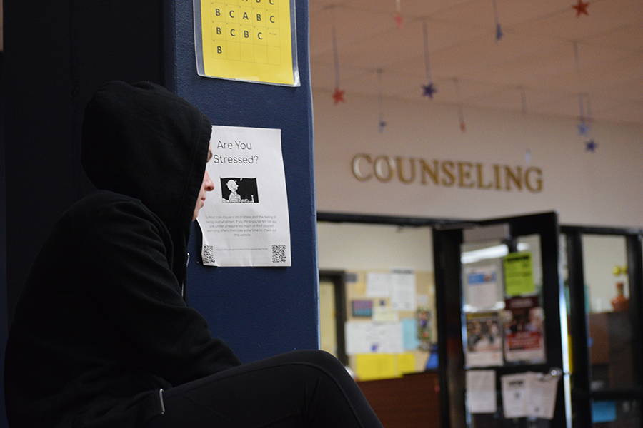 A student sits outside of the counseling office, looking at a poster directed at stressed students. The posters were hung in response to the rising anxiety levels of students. Because of busy schedules, counselors have limited time to deal with the emotional needs of students, and so students are forced to look elsewhere for help.