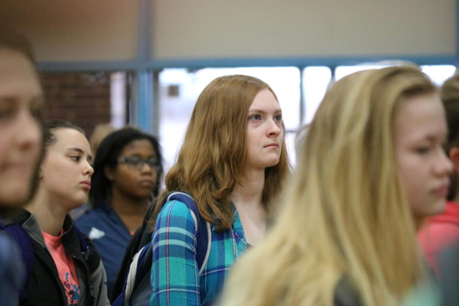 """Sophomore Maddie Hoffman solemnly listens to speakers as they speak about recent school shootings in United States. Over 200 students joined Hoffman in the gym. """"I really wanted to do something to support the cause, even if that just showing my support at the walkout,"""" Hoffman said. """"Some of the information really hit me hard and strengthened my resolve to help."""""""