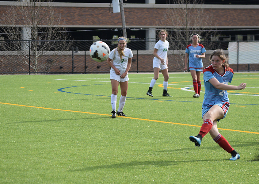 Junior Kaleigh Kastberg swings into a free kick, turf flying into the air. The varsity girls competed against Nerinx Hall on April 13.