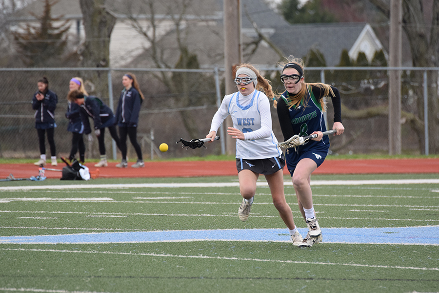 "With her eye on the ball, freshman and midfielder Megan Leahy competes for the ball in a game against Marquette. This is Leahy's first year to play competitively. ""I like that the game is really fast paced, but I also really like that in lacrosse, you have to rely on other people to make everything happen,"" Leahy said."