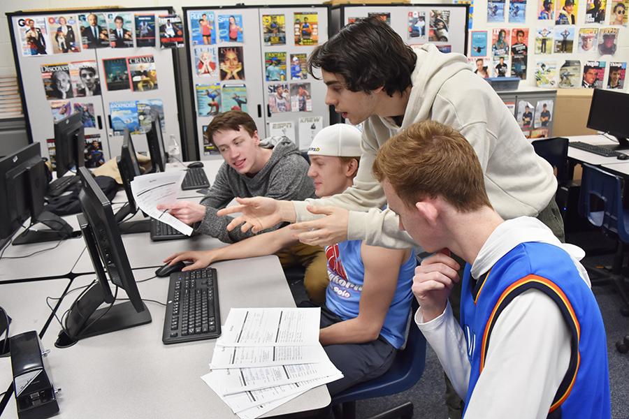 Seniors James Banks, Jackson Piles, Lorenzo Giganti and Jack Cromley look through Blue Brew applications.