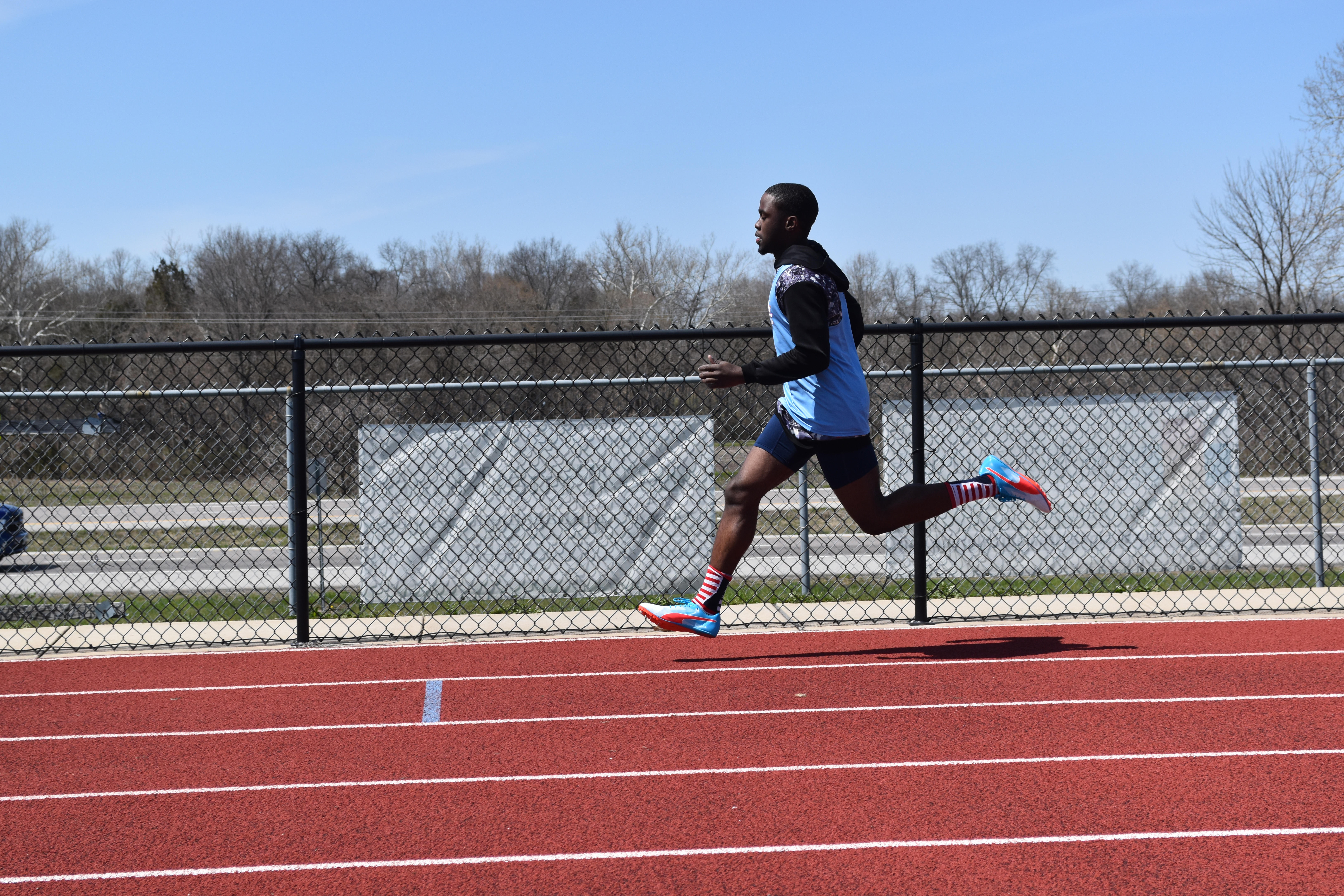 """Striding out on the back stretch, senior Reggie Burns races the 400 meter dash. Burns finished fourth in the event with a time of 53.85 seconds. """"I was feeling a bit under the weather so I couldn't perform at my best, but I was able to recover by the 4x400 meter relay,"""" Burns said."""