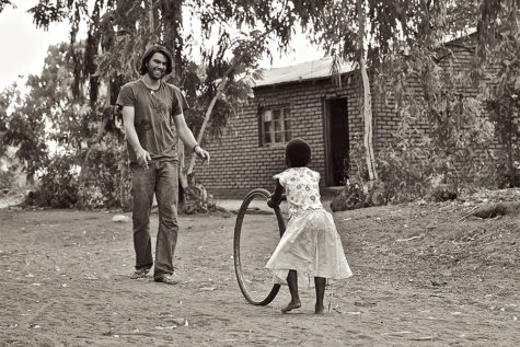 David Peterka rolls a bike tire back and forth with Hope in Malawi. Hope is the daughter of a friend of Peterka's who is a pastor in a village church.