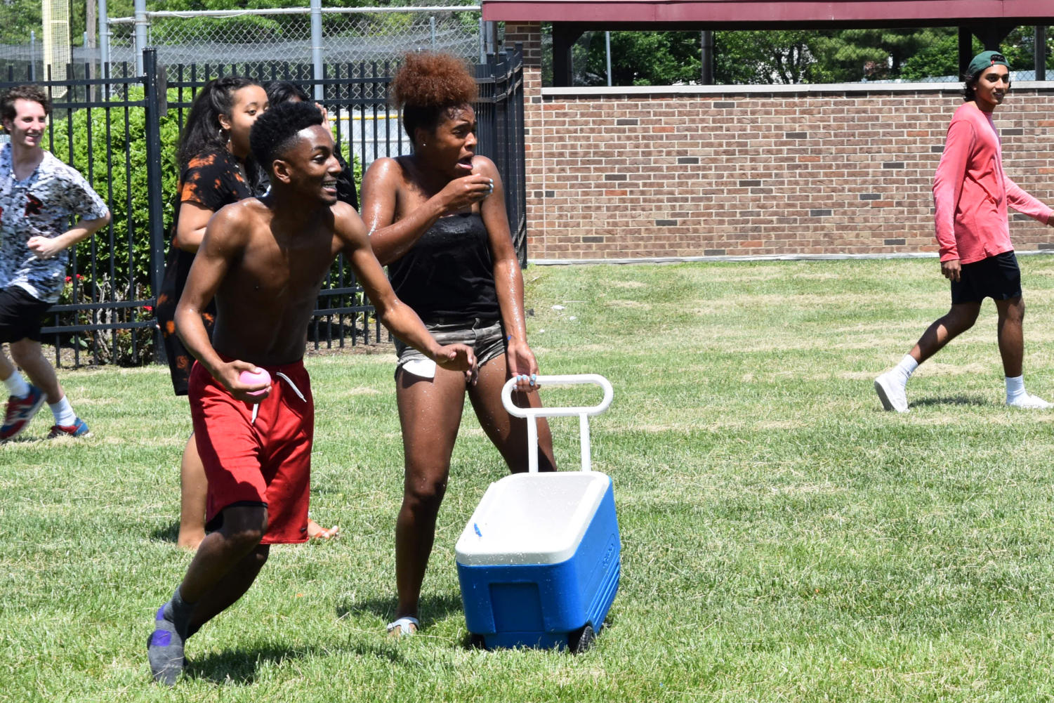 Mouth dropping in shock, junior Harmauhny Faulkner clutches onto a cooler full of water balloons as she is pelted by her classmates. The Junior Class began the tradition of a water balloon fight on the last day of school as a way to kick off their last summer before senior year.