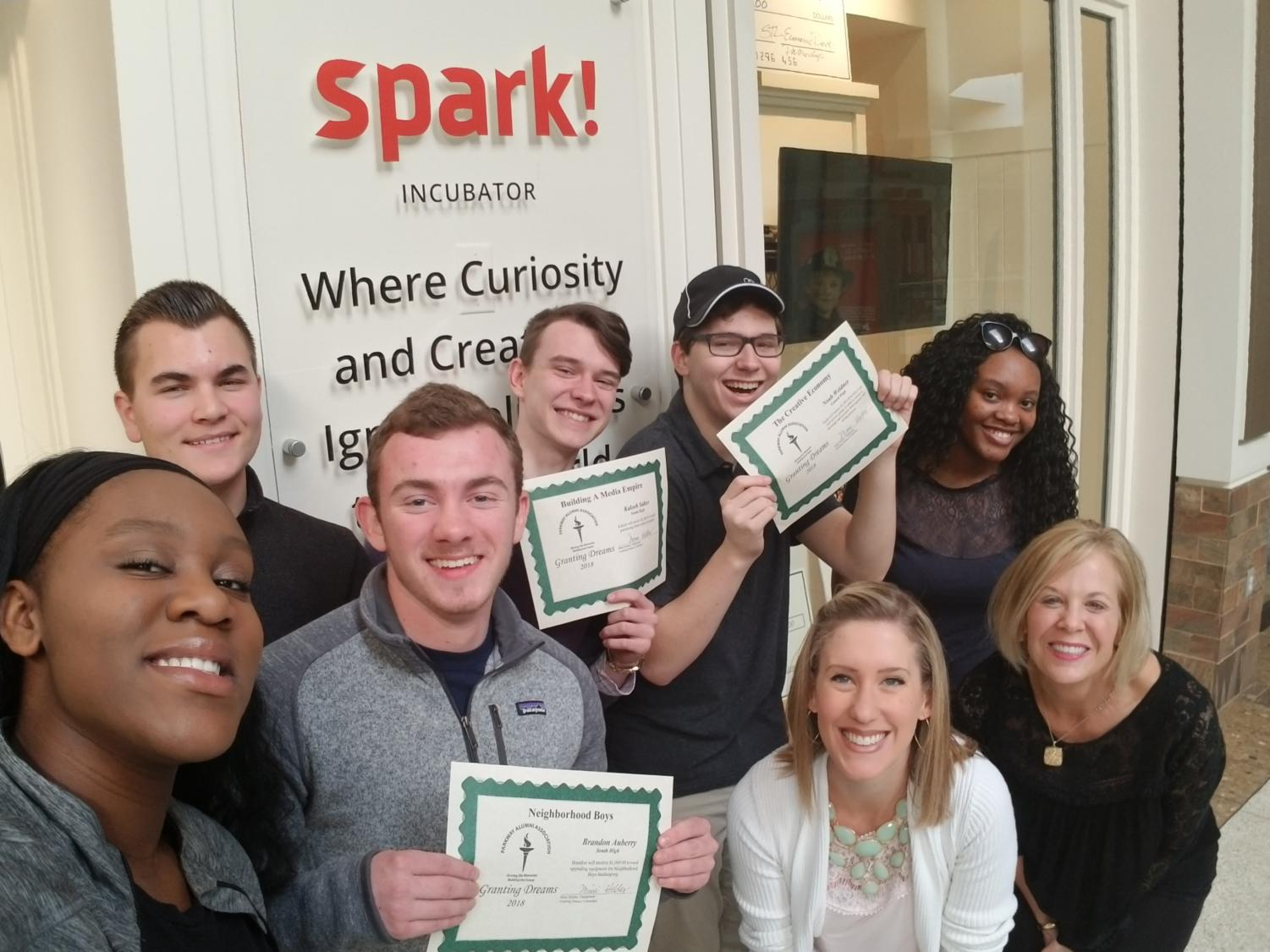 "Leah McCoy stands with the Spark! Students who won $1,000 Phelps Entrepreneurship grants from the Parkway Alumni Association in 2018. McCoy loved working with Spark! students because she thinks the students are what makes the program special to her. ""It has been fun and inspiring to see how they evolve through the year each year. I've been so impressed with the way the students put themselves out there to network and build connections with mentors and others who can help them in the business community,"" McCoy said."