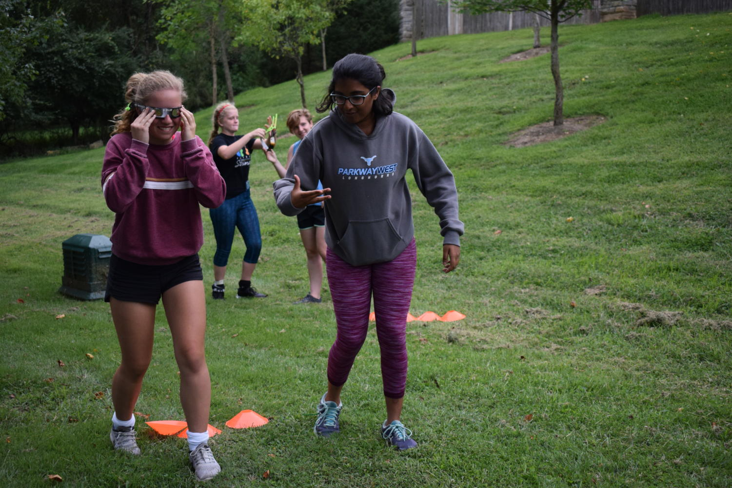 "Navigating an obstacle course, sophomores and JV field hockey players Haley Keller and Rishita Nannapaneni work together to compete against their teammates in a bonding exercise. In preparation for their first game of the season Aug. 24, both the JV and Varsity teams got together for their annual Pasta Night dinner at their Head Coach Dawn Callahan's house. ""I really wanted to win because I'm really competitive, but it was hard with those eclipse glasses on,"" Nannapaneni said. ""I loved bonding with the team. In order to play good as a team, you have to be connected outside of the game because then you know you can rely on them to be there for you in the game and in real life."""