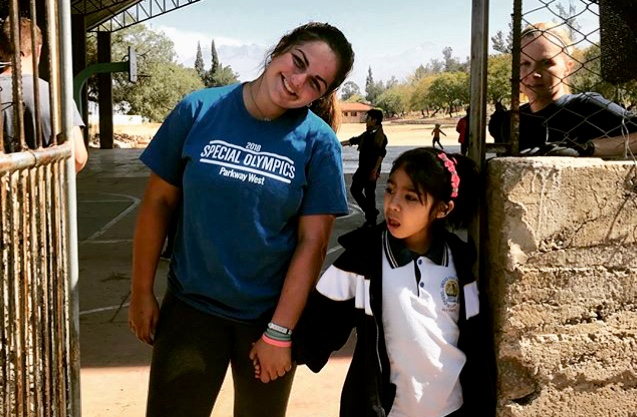 "Holding hands with a student in Cochabamba, junior Kelly Wehrmeister spends her breaks dancing and playing with the local children. On the few days they had off, the group went cave spelunking and visited the tallest Christ statue in the world. ""I'm the happiest when I'm serving others,"" Wehrmeister said."