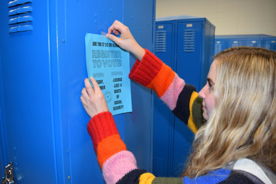 Hanging a flier on a locker, junior Sabrina Bohn raises awareness for the upcoming voter registration event Sept. 18. The campaign seeks to increase youth voter turnout ahead of the 2018 midterm elections.