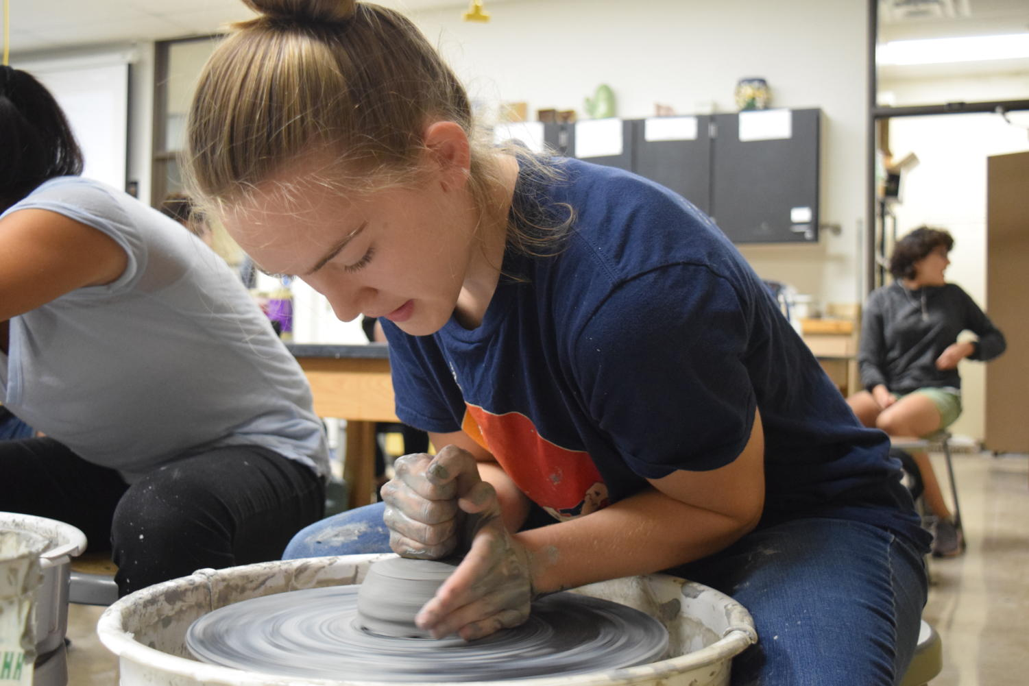 "Molding the center of a clay bowl, sophomore Megan Gordon leans over a pottery wheel in Clay Club. Although Gordon just started experimenting with clay, she has created art with other mediums like paint and is currently taking ceramics. ""I'm not very good with words, and I'm not very good with writing things down because of my dyslexia,"" Gordon said. ""I'm better with painting a picture because I learn very visually, so I'm able to transfer that to the picture. I feel like sometimes my art can speak for me."""