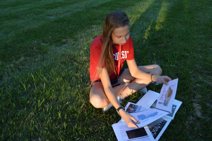 "Junior Lauren Beard reads weather pattern graphs after attending an Earth Sciences camp this summer. At the camp, Beard explored her passion for meteorology with students from all over the United States. ""[I] thought it was a great opportunity to see if this is something that I'm really interested in,"