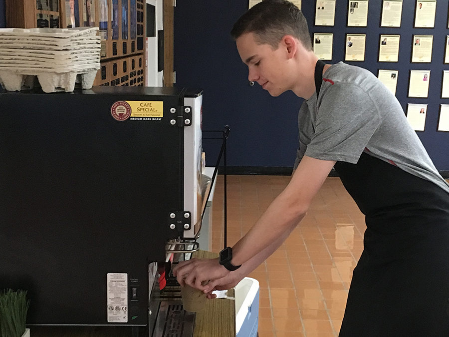 "Using the latte machine, Blue Brew crew member and junior Pierce Burns prepares an order for a customer. The crew members and Marketing II students are learning from and adapting to the wants of the students. ""Some people may have noticed our new straws. We wanted to get away from Community [Coffee's] straws and use paper ones, which was a request, because it is more environmentally friendly,"" Burns said."