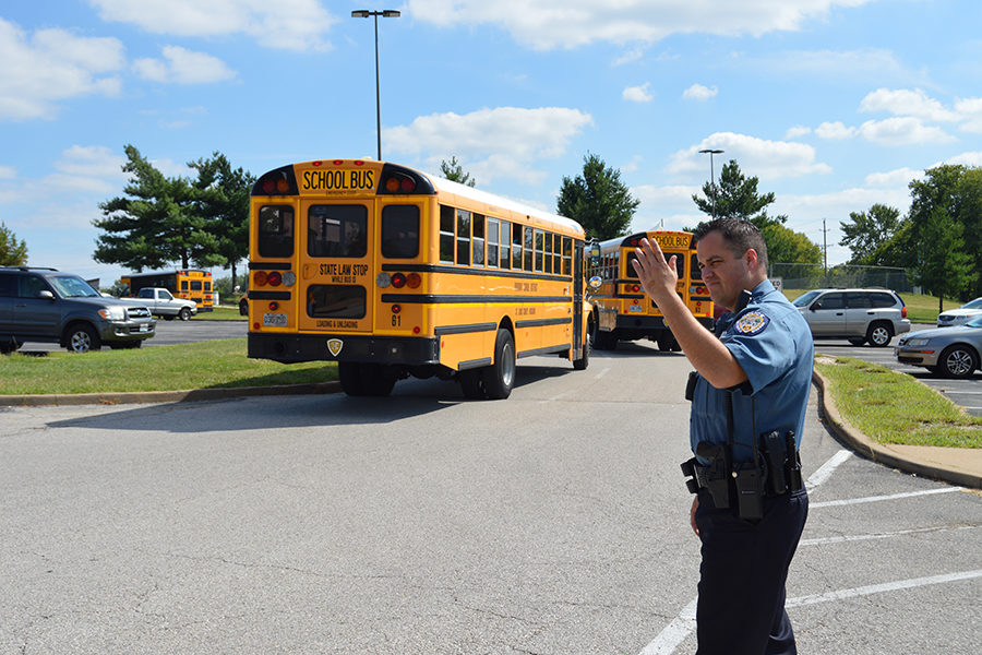"""Student Resource Officer Zeus Hernandez directs traffic in the parking lot. Hernandez has been working as an SRO for the past five years, but this is his first at West. """"Like any profession [in police work], you are always aspiring to do different things, better things,"""" Hernandez said. """"I love my job."""""""