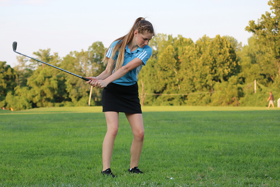 "Chipping her ball at a target, junior Ava Pfeil shows off her skills at Red and Blue night. This is her first year on the team, one of six new people on JV. ""I decided to join [golf] because I wanted to do another sport in the fall [in addition to cheer] and golf seemed like the most fun one because you can chill with friends and relax,"" Pfeil said. ""My favorite part of the season has been the team bonding because since we're a small team we can get really close."""