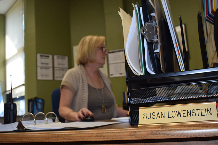 """Secretary Susan Lowenstein works on her computer to update the school schedule for September. Lowenstein works with Principal Jeremy Mitchell on the overall workings of the school rather than with a specific grade level. """"Secretaries want people to be comfortable around them,"""" Lowenstein said. """"They almost act a counselor sometimes."""""""