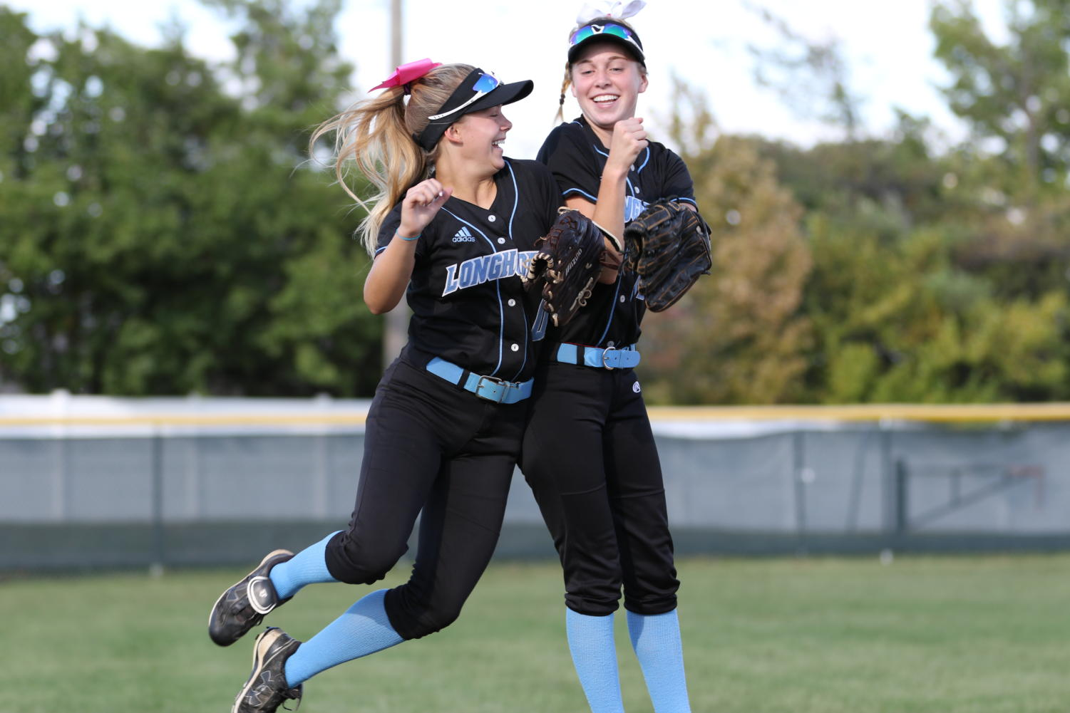 "Rallying together during a home game Oct. 8, senior Alexa Abney and sophomore Emma Breidecker shoulder bump at the start of the varsity softball game against Ladue High School. Throughout the season, the varsity team mentally prepared in between innings by hyping up their fellow teammates. ""Usually before every inning the infielders ran around and high fived each other before the batter came out,"" Abney said. ""Us outfielders always got together and shoulder bumped or chest bumped."""