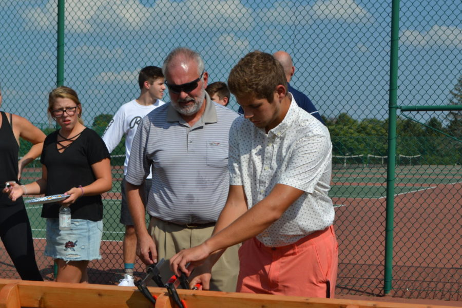 "With his father watching, junior Matthew Hopper attaches a plaque to his bench commemorating the life of Brynn Haun at the senior night ceremony for the girls' tennis team Sept. 20. Hopper chose to create the bench for his Eagle Scout Service Project. ""I've learned a bunch of stuff from Boy Scouts,"" Hopper said. ""From living out in the wilderness by yourself to being a better leader, helping younger people, helping older people, just being a better person, you learn life skills."""