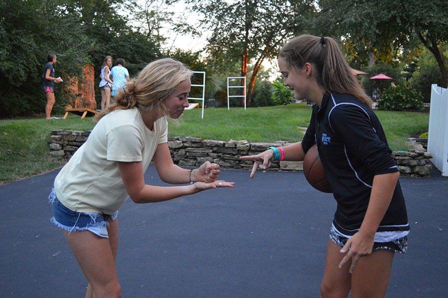 Playing+rock%2C+paper%2C+scissors+to+decide+who+gets+the+ball%2C+senior+Natalie+Butler+and+freshman+Ella+Roesch+play+a+game+of+pick-up+basketball.+The+team+held+a+backyard+picnic+Sept.+15+following+the+Paul+Enke+invitational+earlier+that+morning.+%E2%80%9CWhat+makes+our+team+unique+is+the+welcoming+and+encouraging+atmosphere.+I+don%E2%80%99t+think+other+teams+have+that+as+much%2C%E2%80%9D+Natalie+said.+%E2%80%9CRunning+is+very+hard+and+just+to+be+in+a+community+of+such+hardworking%2C+tough+and+strong+girls+is+really+special.%E2%80%9D%0A