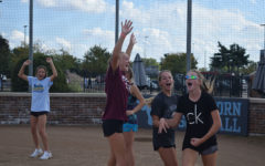 "Hands in the air, members of the softball team, celebrate together at home plate. The team played kickball during practice Oct. 5 for some team bonding. ""[After team bonding activities] girls who I didn't feel like I could talk to before I was able to talk with because I now knew we had things in common and could joke around,"" Leahy said. ""It helped expand my friendships of the team."""