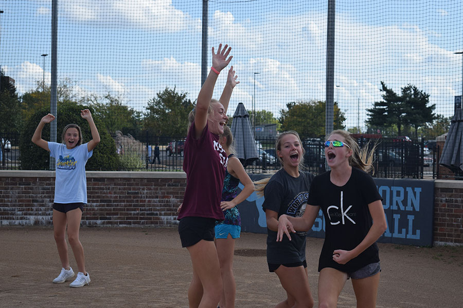 """Hands in the air, members of the softball team, celebrate together at home plate. The team played kickball during practice Oct. 5 for some team bonding. """"[After team bonding activities] girls who I didn't feel like I could talk to before I was able to talk with because I now knew we had things in common and could joke around,"""" Leahy said. """"It helped expand my friendships of the team."""""""