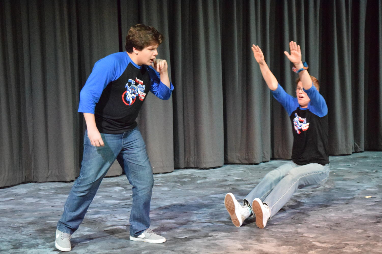 """Throwing himself to the ground, senior Hayden Riehl and freshman Ross Harter improvise a scene together. Harter and Riehl were on team """"Fashion Disaster"""" as part of the show's """"Perfect Storm"""" theme."""