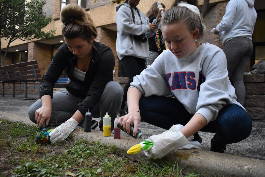 Squatting+in+the+Peace+Garden+Wed.%2C+Oct.+17%2C+senior+Brianna+Vietmeier+and+senior+Women+of+West+Officer+Jessica+Goedeke+tie-dye+shirts.+In+an+effort+to+create+a+sense+of+community%2C+30+members+met+at+7+a.m.+to+talk%2C+tie-dye+and+bond.+%E2%80%9CWe+wanted+girls+to+feel+supported+and+comfortable+coming+to+the+club+and+listening+in+on+their+experiences%2C%E2%80%9D+Goedeke+said.