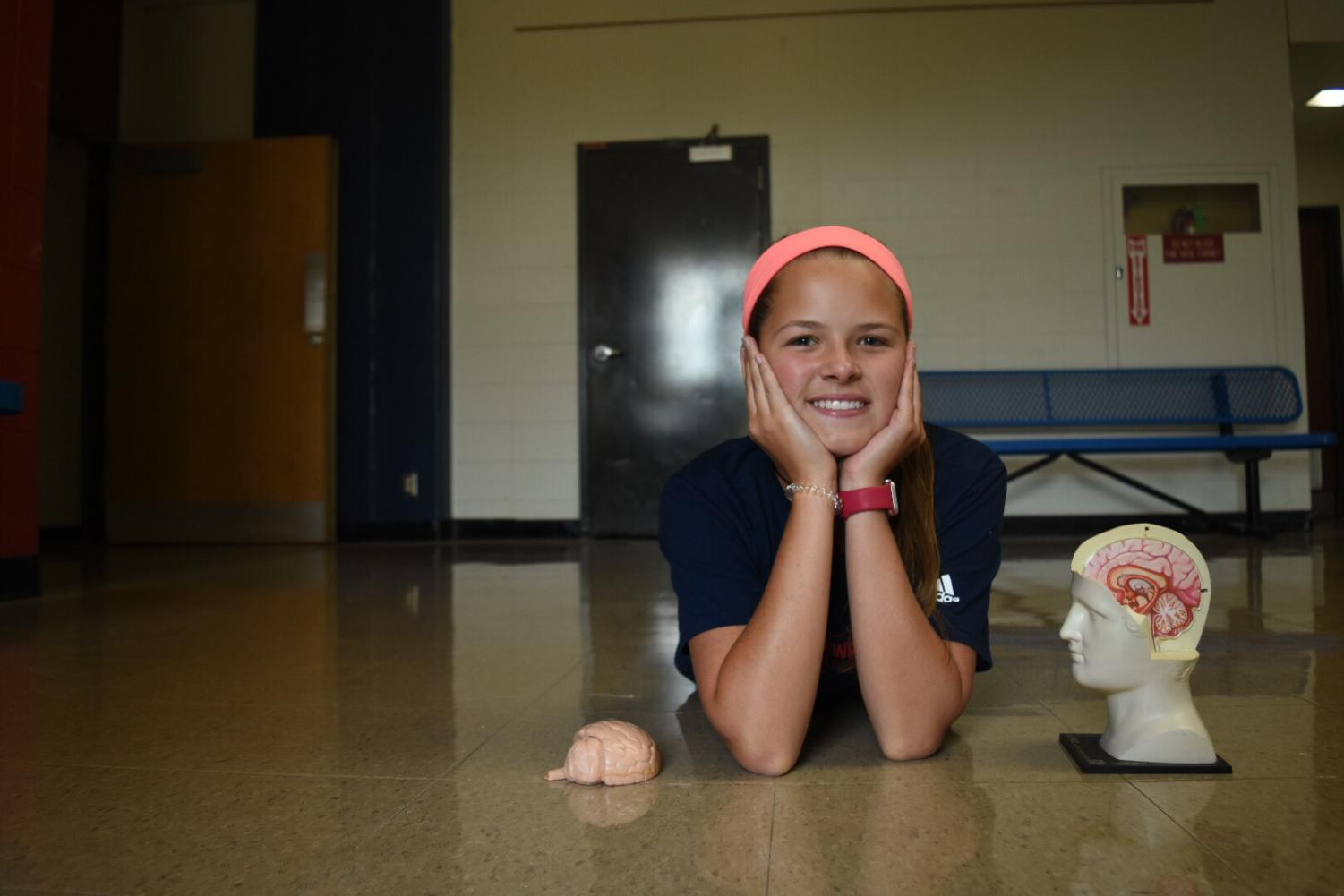 Freshman Giselle Bauer poses with a model of the human brain. Bauer has a brain tumor that causes seizures and has undergone four surgeries to minimize the tumor's size and effects.