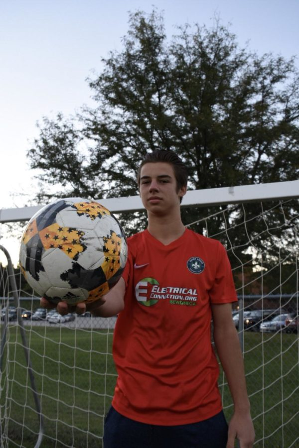 """Holding up a soccer ball, junior Jansen Miller dons his soccer jersey in front of a goal. Jansen has played soccer with the St. Louis Football Club Academy for three years. """"The advantage is that [STLFC] are good role models, who have helped me not just in soccer, but in life as a professional because that's their job. That's their life and that's what I want to do,"""" Miller said. """"Seeing them and what they do every single day, that's my goal."""""""