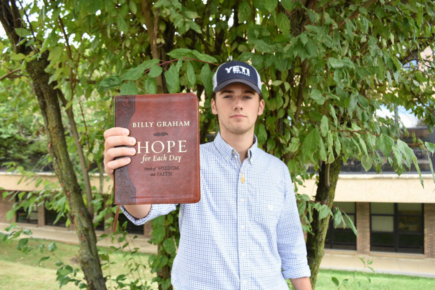 Holding up a Billy Graham devotional book, senior Will Creemens proudly displays his faith. Each day, he reads the devotional and accompanying verses for that day.