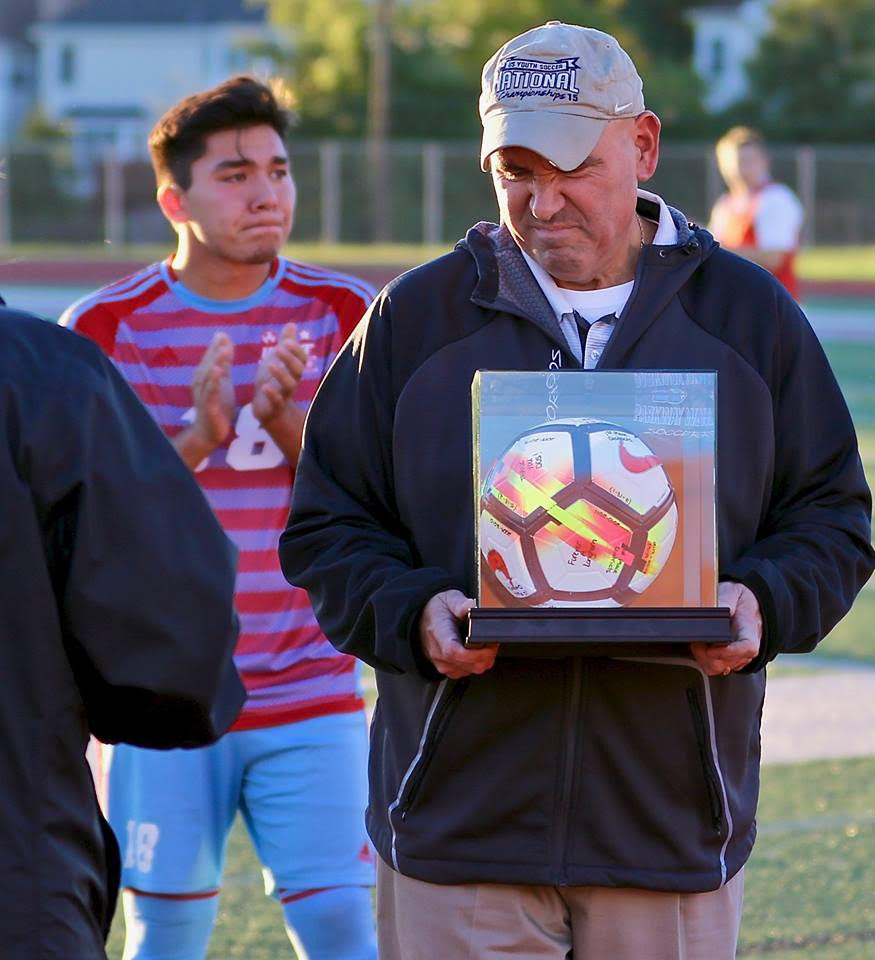 """While being presented an award for coaching 11 years on senior night, varsity head coach Michael Skordos and senior Harry Skordos cry for their last home game. M. Skordos has coached his son, H. Skordos, since he was young. """"It's really rewarding that my dad has been able to coach me for so long. The fact that he waited until I graduated to retire means a lot, especially that we could spend our last home game together,"""" H. Skordos said."""