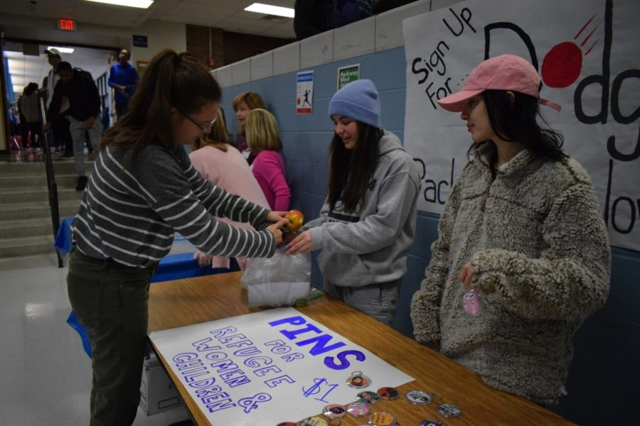 Buying+a+pin+from+seniors+and+Feminist+Club+co-leaders+Lizzy+Calvert+and+Allani+Gordon%2C+senior+Kaitlyn+Taylor+helps+Feminist+Club+in+their+mission+to+donate+money+towards+immigrant+and+refugee+women+and+children.+The+club+sold+pins+and+keychains+for+%241+each.+%E2%80%9CThe+concept+of+being+active+in+West%E2%80%99s+community+and+volunteering+in+West+County+and+the+St.+Louis+community+is+a+great+experience%2C%E2%80%9D+Calvert+said.+%E2%80%9CTo+be+able+to+donate+money+to+a+program+that+will+benefit+women+and+others+is+always+a+nice+feeling.%E2%80%9D