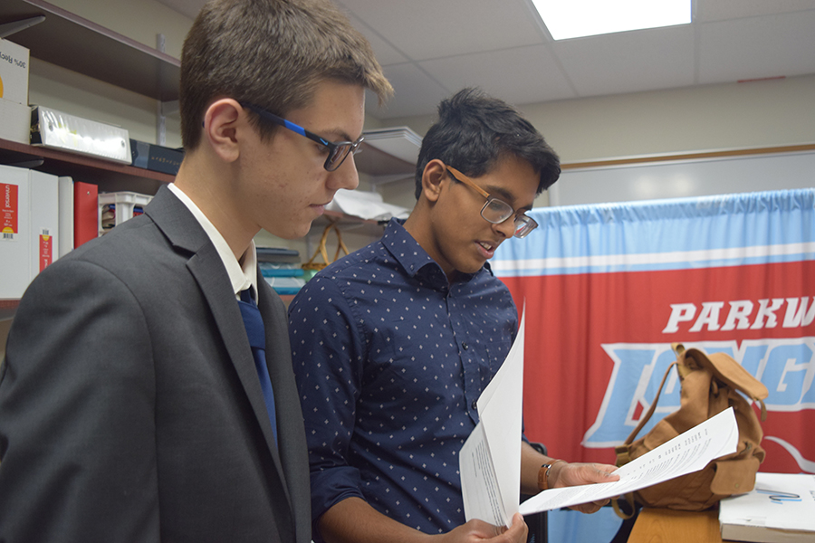 Sophomore Tyler Kinzy and senior Gokul Venkatachalam converse as they review a document. The two were inspired to pursue mental health activism after alumni Haran Kumar passed away June 15.