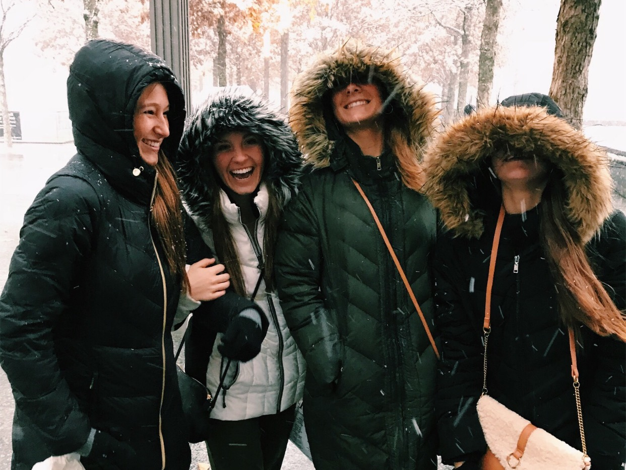 "Smiling through a sudden snow fall, juniors Caroline Briscoe, Reagin Ward, Jenna Mercer and Madison Foelsch put their hoods up as they navigate through the streets of New York. Marketing students arrived in the city Wednesday to attend seminars, shop and explore. ""I was already so excited for a day with my best friends, but when it started snowing is when I really felt like I was in a movie,"" Mercer said."