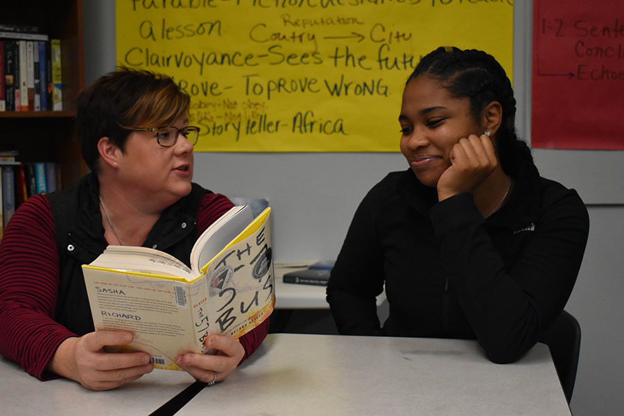 "Book in hand, NEHS sponsor and English teacher Kim Hanan-West discusses with sophomore Trinity Peoples. When former student, Gabe Davis asked Hanan-West about an English honors society, Hanan-West did some research and started applying to NEHS. ""I would encourage any student who is passionate about books, literacy and writing to apply,"" Hanan-West said."