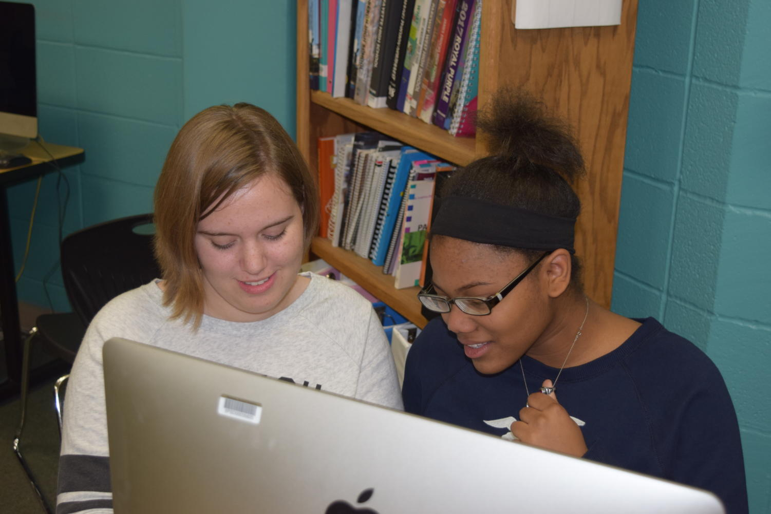 "Providing each other feedback, alumni Sydney Kinzy and Gabrielle Thompson revise fiction stories they wrote. Both were members of the literary magazine production club, Reflections, which met once a week on Mondays. ""Any clubs that took place before school or on Fridays, I had no possible chance of participating in them due to either the city buses showing up too late to school or there being no transportation available at all,"" Thompson said."