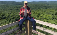 Sitting atop the viewing tower fence, junior Nathan Clem celebrates making it to the summit of the Porcupine Mountains. Clem and his friend Jacob Carpenter led a week-long expedition in the mountain range that included a trip to the summit.