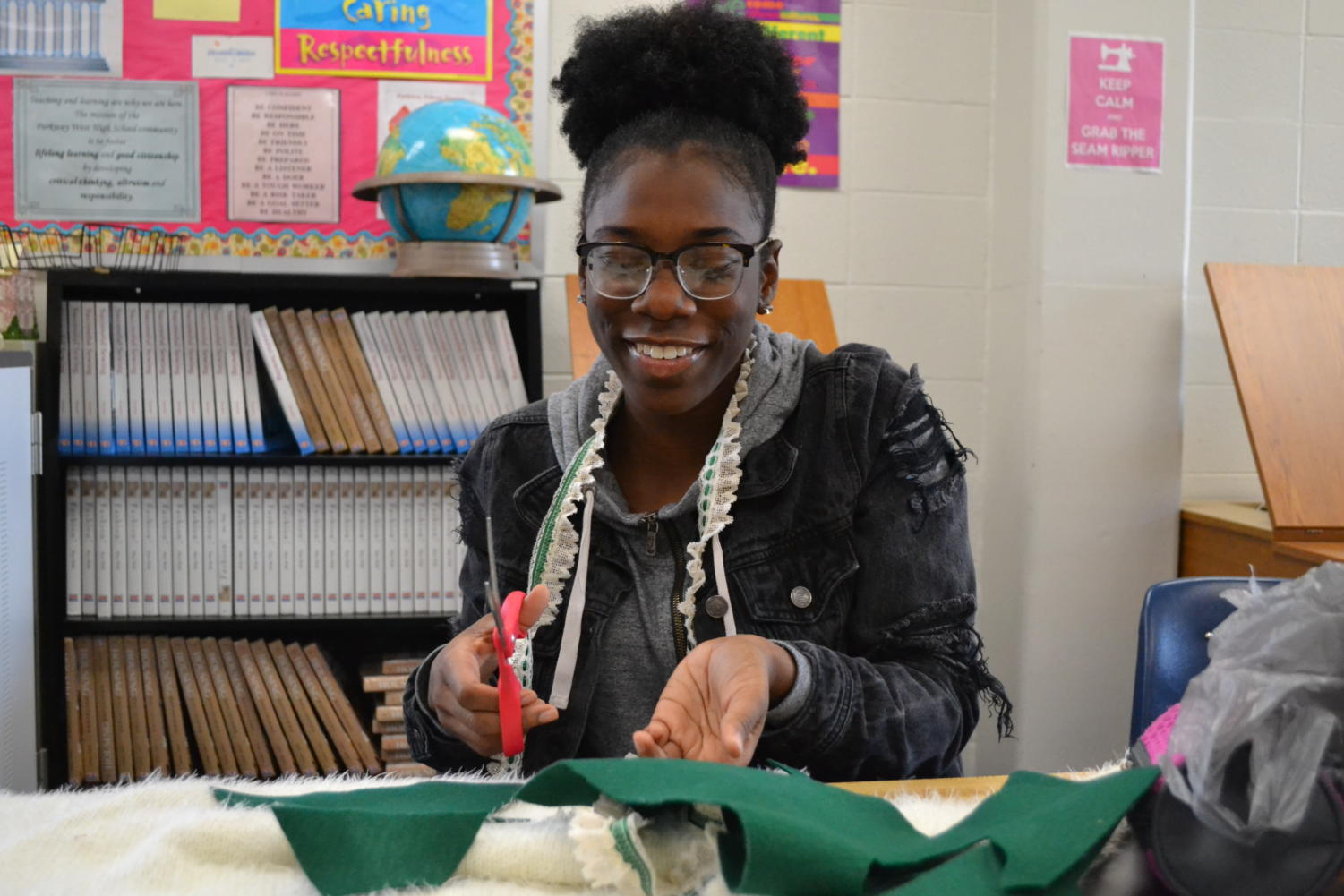 "Cutting fabric with scissors in hand, junior Meela Abbey decorates her ugly Christmas sweater during a Fashion Club meeting after school on Nov. 29. Members of the club gathered in Family and Consumer Science teacher Renee Broemmelsick's room to make their own holiday sweaters. ""Since they were supposed to be ugly, I had to make mine ugly, but like a cute ugly, it had to have some potential,"" Abbey said."