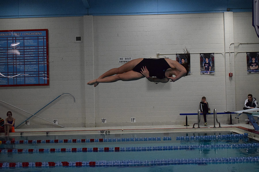 """5:11 p.m. In midair, junior Claire Lynn completes a one and a half twist dive at a home meet Thurs., Jan. 10. With swim and dive conference and state coming up, Lynn used this meet to practice higher level dives. """"I've been working on some new dives to work up to conference and state, and I did them all, so I was happy about that. Right now, I'm just trying to improve them to get a state cut,"""" Lynn said. """"I went to state last year, but I was one of the last people to get accepted, so I'm really looking forward to going back, improving my place and being more competitive with the other divers."""""""