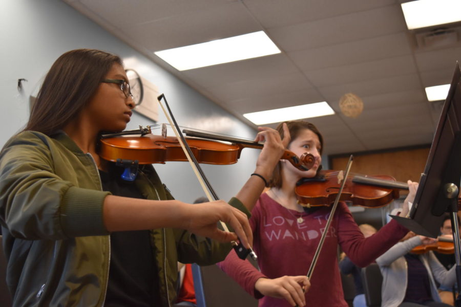 1:23 p.m. Focusing on the music, sophomore Salma Ahmed and junior Theresa Monteleone play with the Symphonic orchestra during class. The Symphonic orchestra attended a 12-hour festival at University of Missouri-St. Louis Jan. 8.