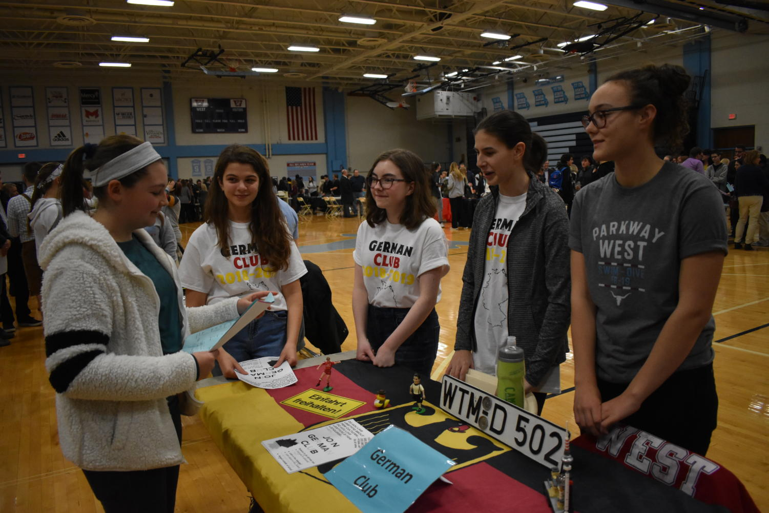 """Introducing eighth graders to the highlights of German Club, freshman Anna Csiki-Fejer stands with sophomores Claire Reifschneider and Eva Phillips at the German Club table during Curriculum Night Jan. 15. """"We printed out flyers, passed them out and told the students involved in any foreign language about our club because we are open and welcoming to all students, in German or not,"""" Csiki-Fejer said."""