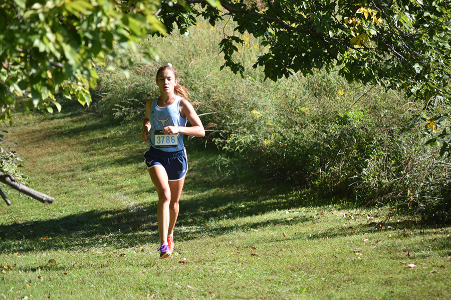 "Leading the race, senior Chloe Hershenow competes in the conference championship. Hershenow plans to continue her running career at the university of Tulsa in the fall. ""Being able to run collegiately is a culmination of having coach Cutelli and Coach John because they are both great coaches and who have pushed me and having the team I have had; they have really supported me,"" Hershenow said."
