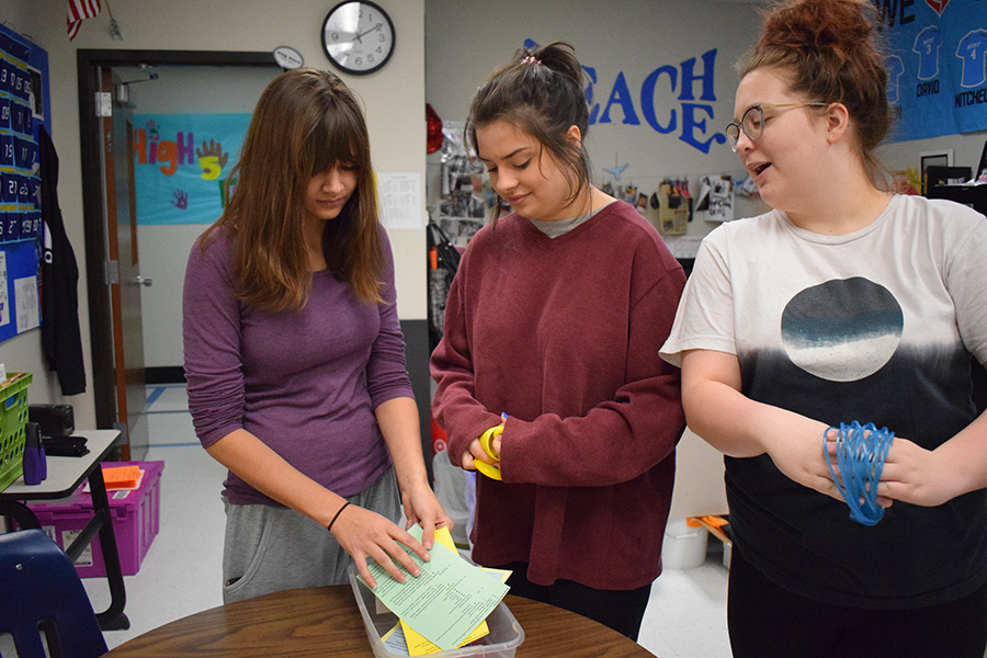 Seniors Jasmine Gilroy, Julia Molino and Sam Fuller perform inventory on their Calming Box in the Science ASC.