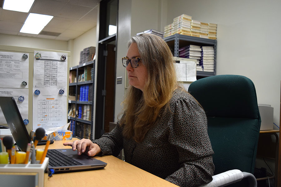 Inside the English Concepts Center, teaching assistant Rose Rouner works on her laptop. Rouner spends most of her mornings answering emails for parents of students in the Eighth Grade Acceleration program.