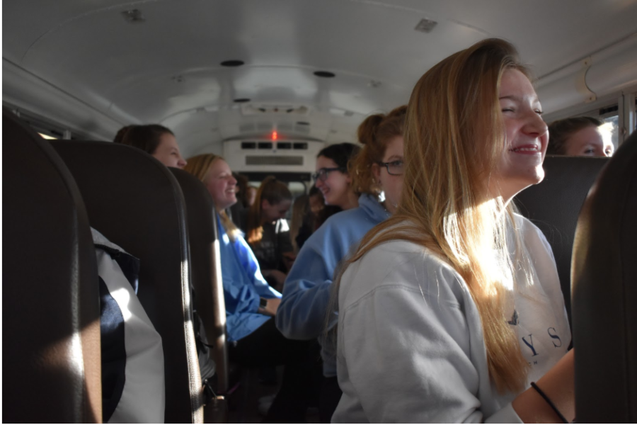 """4:07 p.m. Laughing on the bus ride to a swim meet at Lindbergh High School, senior Alyssa Theroux enjoys the comradery of her teammates. On the way back to school after every meet, the girls swim and dive team sings a song once they reach Clayton Road. """"My favorite part is when we sing the chant: 'Clayton Road, take me home to the place where I belong…'"""" Theroux said. """"Bus rides are always fun, they're a great place for team bonding."""""""