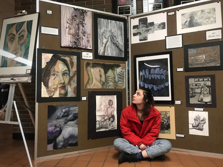 "Sitting criss-crossed in front of her concentration, senior Allani Gordon showcases her work at the Parkway West District Art Show on Thursday, Jan. 24. Throughout the semester, AP art students focus on one theme, or concentration, to guide their projects. ""I chose decay and wanted to depict beauty within decomposition with a feminine touch,"" Gordon said."
