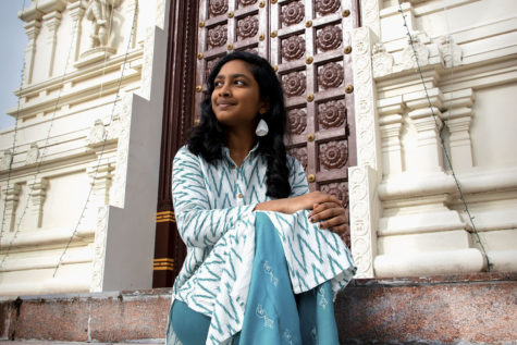"Sitting in front of the Hindu Temple of Saint Louis, freshman Brinda Ambal dons traditional attire. Ambal has been a member of her temple's Youth Group since 2016. ""In St. Louis I can make [Hinduism] my own. The small things aren't that important, it's about how you live your life and follow the religion as a whole,"" Ambal said. ""A lot of our Holy Texts have stories about courage and trusting yourself so that you are best able to serve others."""